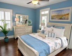 Luminous Coastal Beach Art brings a warm glow to this blue beachy coastal cottage bedroom. Featured here: http://www.completely-coastal.com/2016/05/the-colorful-coastal-cottages-at-ocean-isle.html