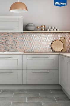 This on trend blush copper and metallic mosaic tile shot has a refined sophisticated look. The simple light grey shaker kitchen doors are teamed with slate grey floor tiles and a solid quarts worktop. Shaker Kitchen Doors, Grey Shaker Kitchen, Grey Kitchen Cabinets, Shaker Cabinets, Kitchen With Grey Floor, Pink And Grey Kitchen, Grey Cupboards, Grey Shelves, Kitchen Ideas With Copper