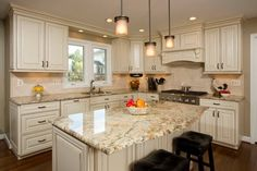 white kitchen cabinets Yellow river granite countertops mini pendant lights over kitchen island