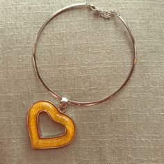 Silver choker with heart shaped pendant This choker comes with an adjustable chain at the top to fit perfectly around your neck. The heart pendant is a soft amber colored glass with silver trim. A beautiful piece to be worn with a sundress this summer. Jewelry Necklaces