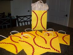 I decorated these 12 goody bags to look like softballs. They will be filled and exchanged with the first team we play at our 2013 World Series. The bags were 2 for $1 at the Dollar Tree and the red rick rack was $1.66 for 2.5 yards. I bought 3 packs of rick rack which worked out perfectly for the 12 bags. I used Elmer's glue instead of hot glue so I could move the rick rack into position as needed. Finished product cost: $1 ImaMom2three