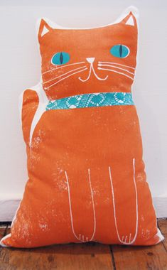 cat shape adds to the cuteness of the design, creates more impact and crosses the cushion/toy divide.