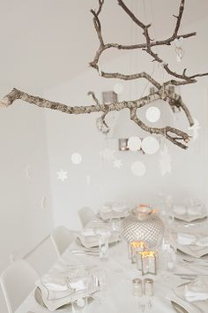 Branches hanging from ceiling. With glass globe tea lights or small jar lights hanging from them. Would also be gorgeous with pine tree branches and Christmas tree decorations.