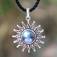 Pearl flower necklace, 'Sunflower Blue': A radiant sunflower reveals its blue mabe pearl heart, the birthstone of June, in a stunning design from Putu Putri. The pendant is crafted with sterling silver and glistens with classic Balinese stylizations. The pendant centers a braided silk cord.