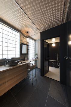オリエンタルな香り漂うインテリアデザイン。ガラスブロックを通して自然の光が柔らかに空間を包み込みます。アジアンテイストの網代天井に、墨入モルタルと塗装で仕上げたブラックの壁のコントラストが絶妙。床は大判の大理石を貼りスッキリと。アンティークなアクセサリー小物や額縁をつけたオリジナルミラーが美しく映えます。多様な素材が調和を奏でるサニタリーのインテリアコーディネートになりました。幅広の引出し収納キャビネットに、ちょこんと乗った丸い手洗いボールがおしゃれです。バスルームへの入口は段差を無くしてバリアフリーに。ハイドアにはスモークを貼りました。 Japanese Architecture, Sweet Home, Bathtub, Bathroom, Yellow, Standing Bath, Washroom, Bathtubs, House Beautiful