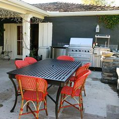 Pops of Color  Add a summer splash of color to an outdoor kitchen with bright chairs. In this space, red woven chairs show off against the black table and stainless-steel appliances. Love!