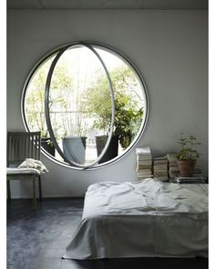 A round window is traditionally referred to as an oculus. They are traditionally placed high up on building facades or at the pinnacle of domes. Installing one in a bedroom is a charming touch. Go large scale to keep if from feeling too much like a porthole. |Beautiful Living Spaces|