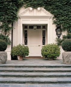 Love the traditional detailing of this front door with the oversized potted bushes and ivy.