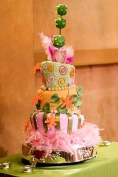 Adorable and colourful three tier fun cake design, in pink, orange and green, decorated with feathers, handmade gumpaste leaves and florals.