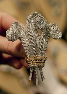 originally made for the Duchess of Windsor , it's the symbol for the Prince of Wales. When she died in 1986 , Prince Charles got into a bidding war at the auction of her jewels with Elizabeth Taylor. Charles lost . It remained with Elizabeth until her death .