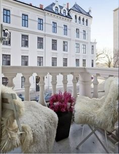 Layered sheepskins on simple metal folding chairs .. so chic!
