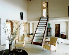 In the home of Consuelo and Gianni Castiglioni, an adobe staircase, inspired by a trip to Yemen, leads from the sitting room, with its 1950s Italian chairs, to the bedroom in Formentera, Spain. Photographed by François Halard, Vogue, January 2004.