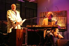 "1960s synthesizer pioneer Jean-Jacques Perry, left, in his 80s, with current partner Dana Countryman. Known for ""Baroque Hoedown,"" the theme of the Main Street Electrical Parade at Disneyland; such discovery and filmic use of his music is a trend that continues to this day ... current info @ his official Website, http://www.jean-jacquesperrey.com . Wikimedia Commons photo by bthrewww, shared under Creative Commons license, details @ http://creativecommons.org/licenses/by-sa/2.0/deed.en ."