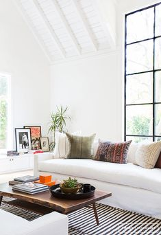 Kilim pillows / cushions and a striped rug in the sitting room of a laid-back, boho cool Californian home. Amber Interiors.