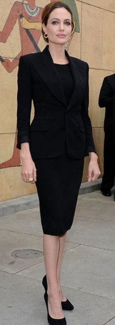 Angelina Jolie. power dressing. black slim fit skirt suit. pencil skirt. bun up hair.