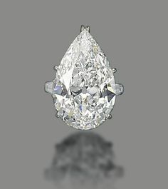 A DIAMOND RING, BY HARRY WINSTON  Set with a pear-shaped diamond, weighing approximately 19.24 carats, to the tapered baguette-cut diamond shoulders, mounted in platinum