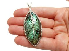This handmade leaf pendant is made of silver plated wire and a genuine labradorite gemstone. It is a stunning green gemstone crafted into a beautiful tree leaf. The size of the gemstone is 40 x 20 mm. For additional 4€, you can order a silver plated chain (there are three lengths