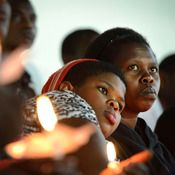 Rwandan women hold candles during a night vigil and prayer for genocide victims at Amahoro stadium. ... The Rwandan genocide was a murderous campaign of majority Hutus against minority Tutsis, triggered by the killing of the Hutu president but planned with racist ideology for years before. It began on April 7, 1994, and ended three months later with more than 800,000 people killed, the fastest genocide in history.  Monday's commemoration honored the dead. But it was also a celebration of how…
