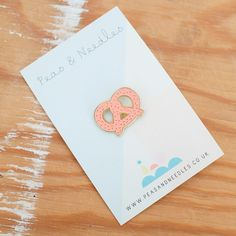 An enamel pin badge with an illustration of a pretzel. x gold enamel. All illustrations by Lucy Davidson Selling Handmade Items, Jacket Pins, Cool Pins, Pin And Patches, Stickers, Pin Badges, Design Reference, Lapel Pins, Pin Collection