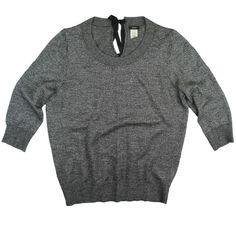 """JCrew Gray Sparkle Charcoal Shimmer Bow Sweater Excellent condition! This silver (official JCrew color name is sparkle charcoal) shimmer bow sweater from JCrew features a tie closure behind the neckline and 3/4 length sleeves. Silver metallic threading in the knit. Made of a wool blend. Light weight. Measures: Bust: 41"""", Total length: 26"""", Sleeves: 19"""" J. Crew Sweaters Crew & Scoop Necks"""
