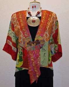 red multicolored kimono style mid-length lightweight jacket on a black base. Brown Frog style button closure. Incredible detail on this patchwork art to wear piece that with a mixture of embroidery, print and solid black detailed jacquard rayon's. Back of top is black jacquard rayon. Open on the sides, no sleeves. 129.00
