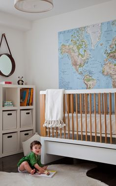 Neutral nursery design with an explorer theme - love the map behind the crib.