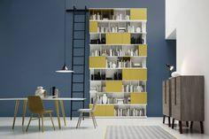Super tall bookshelf with yellow feature shelves and a cool, minimal, scandinavian style dining table. Hoches Bücherregal mit Leiter : Cupboards & shelving by Livarea
