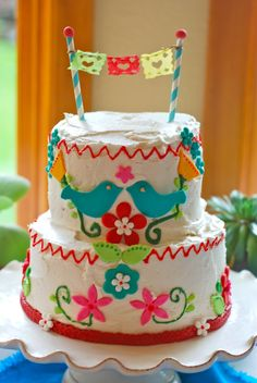 This weekend we hosted a Mexican Folk Art Fiesta for two very special  Señoritas!   Mexican Folk Art Cake  Fondant decorations on a vanilla buttercream cake filled with our own local  raspberry preserves.  Stunning floral arrangement of dahlias and peonies by Allison of Bramble  Floral Design in Portland, OR  Sweet and festive cupcakes  The birthday girls wore these darling floral and succulent head wreaths  which were also designed by Allison of Bramble Floral Design.  Rosy's ...