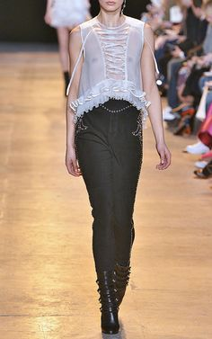 This **Isabel Marant** pant is rendered in stretch suede and features a high rise with an irregular studded self-belt at the waist, studded fleur de lis details at the hips and a tapered leg with stud trim down the sides.