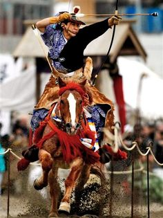 "A mounted archer wearing a Samurai warrior costume aims at a target during an annual ""Yabusame,"" or horseback archery festival, in Zushi, southwest of Tokyo, Japan,"