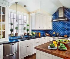 Ocean-blue glazed ceramic tiles have both a cooling and cozy-ing effect in this white, open-plan kitchen. | Photo: Eric Roth