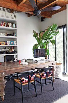Escritorio sobrio con aire inglés. Mesa de lapacho con patas torneadas y sillas 'Wishbone' (todo de Raresh Home).