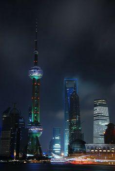 Pudong, centro financeiro e comercial da China, tem alguns marcos arquitetônicos. Na foto do distrito à noite, destaca-se a Torre Pérola Oriental. Shanghai, China.