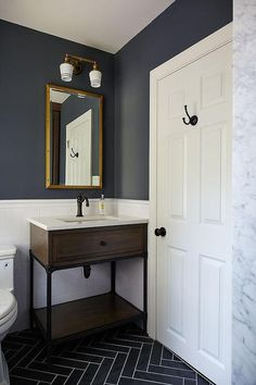 Blue and gray kid's bathroom features upper walls painted dark blue and lower walls clad in white subway tiles lined with a wood and iron washstand and a Restoration Hardware Rivets Medicine Cabinet illuminated by Schoolhouse Electric Irvine Double Sconces alongside a gray slate herringbone tiled floor.