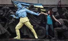 A woman poses for a picture with the figures of Soviet soldiers at the base of the Soviet Army monument, parts of which have been painted in the colors of the Ukrainian flag by an unknown person, in Sofia, Feb. 23, 2014.