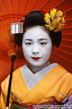 """Komomo, a maiko with umbrella, Kyoto, Japan, 2005 - Komomo is an apprentice maiko (""""dance child"""" or """"half jewel"""") and as part of her training to become a geisha spends 24 hours a day, seven days a week for about five years studying the formal arts such as dance, music and poetry."""