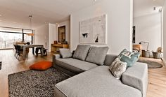 Gray Living Room Sofa On Rug With Pillows And White Wall Panel Decorated By Painting And Recessed Ceiling Lamps Also Wide Glass Wall Design Modern Architecture Demonstrates the Unity between Nature and Interior Home design