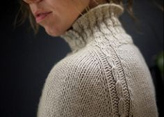 A reversible crossed rib collar flows into the raglan shaping and then down to the side panels of this pullover. Minimal ease, ribbed side panels and a bit of waist shaping give this sweater a close, but not overly tight fit. The turtleneck can be worn buttoned up against a cold wind or left open to show off the reversible stitch pattern. Shown modeled in size 34 on a 33.5 inch bust.