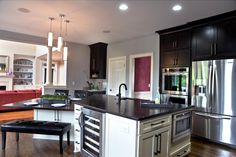 This trendy gray kitchen features black cabinetry and professional-grade appliances, including an island with a built-in wine cooler and microwave oven. Connected to the island, a small dining area includes a black leather bench and chairs.