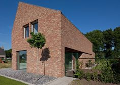 Home in Belgium featuring handmade bricks and a lopsided roof.
