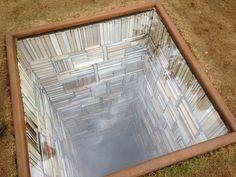 """Susanna Hesselberg, """"When My Father Died It Was Like a Whole Library Had Burned Down"""" (2015) / Photo by Claire Voon for Hyperallergic    For her entry into the biannual Sculpture by the Sea in Aarhus, Denmark, Swedish artist Susanna Hesselberg installed this ominous library that plumments into the"""