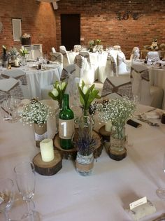 Rustic log slices with candles and hessian and lace wrapped jars with ivory tulips, gypsophilia and lavender