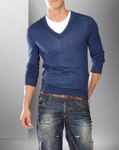 Long sleeve v-neck blue sweater over white and dark denim with brown belt.
