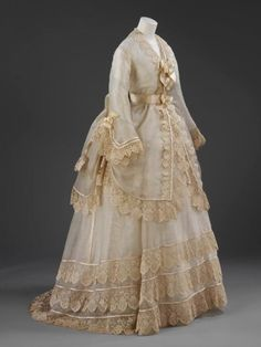 Wedding dress, cream silk gauze with narrow opaque stripe, trimmed with cream silk embroidered net lace.  1874
