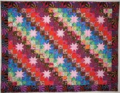 This is a pattern called Star Trip.  It has a controlled number of fabrics rather than the scrappy way I usually work.