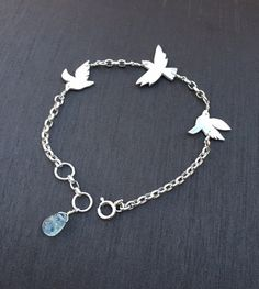 "For the bird lovers! This is a handcrafted fine silver(.999%) bird bracelet with three dainty birds in flight,wire wrapped and linked together by a soldered sterling silver chain.Length:7.5""-8"" max. ($56)"