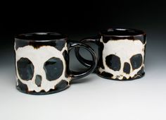 Two warm, dark amber mugs with white zombie-like skulls and crossbones. These were made using a high fire white stoneware clay and fired hot to cone 10 (2300 F). My ceramics are super durable and are made to be used.    These cups have a solid weight with generous and rounded handles. The skull and crossbones are a satin white glaze and are surrounded by a glossy dark amber over the whole rest of the outside, including the bottom. These feel really nice in your hands. Holds about 10 oz/ 295…