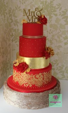 """I must say I think it is one of the nicest cakes I have made to date. It was 18"""" tall + the 4 """" topper. The bottom tier was vanilla sponge filled with vanilla buttercream. The cake was covered with red fondant and decorated with gold edible lace...."""