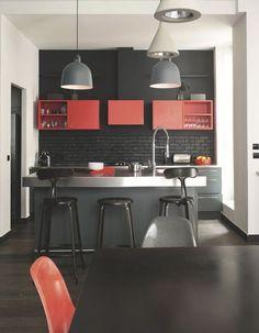 Des touches de rouge réchauffent la cuisine noire de l'appartement
