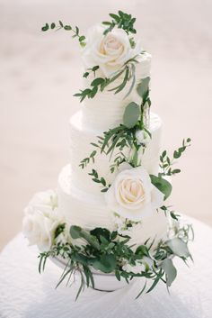Three tier white wedding cake covered in ivory roses: http://www.stylemepretty.com/destination-weddings/2016/08/25/dreamy-beach-wedding-style-session-at-celebrity-destination/ Photography: Darinimages - http://www.darinimages.com/